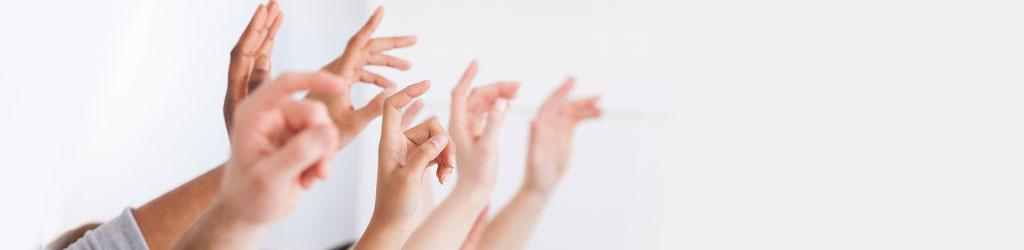 Rehabilitation kommt an – Wissen ermöglicht Vernetzung: Sechs Menschen strecken eine Hand in die Luft.